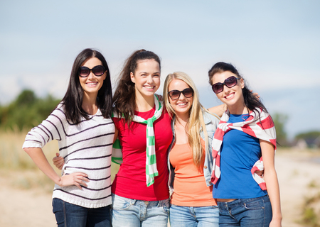 summer holidays, vacation and people concept - happy teenage girls in sunglasses or young women having fun on beach