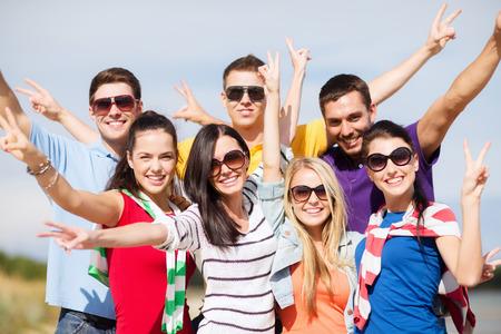 personas saludandose: vacaciones de verano, vacaciones, turismo, viajes y concepto de la gente - grupo de amigos felices que se divierten y que muestra gesto de la victoria en la playa