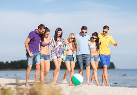 summer holidays, vacation, tourism, travel and people concept - group of happy friends with inflatable ball walking along beach photo