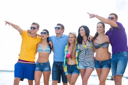 summer holidays, vacation, tourism, travel and people concept - group of happy friends pointing finger and walking along beach Stock Photo