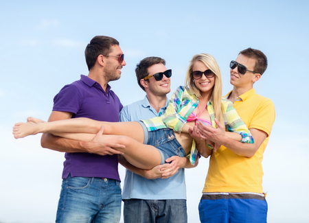 carrying girl: summer, holidays, vacation, happy people concept - group of friends having fun and carrying girl on hands at beach
