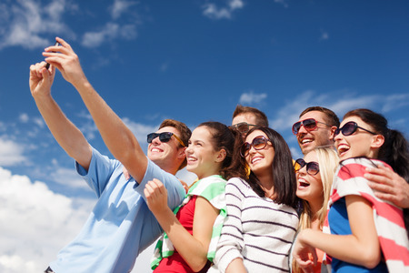 celulas humanas: vacaciones de verano, vacaciones, feliz a la gente concepto - grupo de amigos que toman Autofoto con el teléfono celular en la playa Foto de archivo