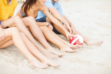 teen girls feet: friendship, summer holidays, sport, leisure and people concept - close up of happy friends legs with beach ball sitting on sand Stock Photo