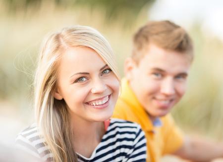 pareja de adolescentes: vacaciones de verano, turismo, viajes, relaciones y personas concepto - grupo de la feliz pareja en la playa