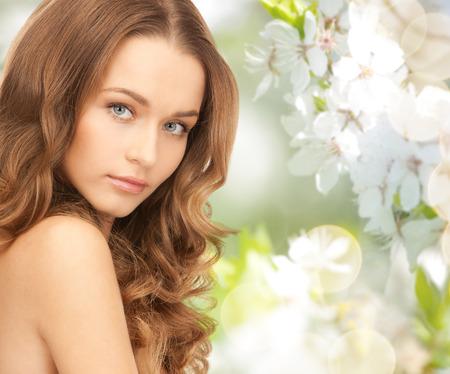 아름다움, 사람들, 여름, 봄, 건강 개념 - 녹색 피는 정원 배경 위에 아름 다운 젊은 여자의 얼굴