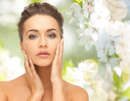 la beauté, les gens, l'été, le printemps et le concept de santé - belle jeune femme de toucher son visage sur fond vert floraison de jardin Banque d'images