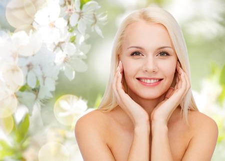 아름다움, 사람들, 여름, 봄, 건강 개념 - 아름 다운 젊은 여자는 녹색 피는 정원 배경 위에 그녀의 얼굴을 만지고