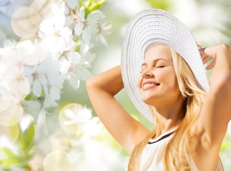 패션, 사람과 여름 휴가 개념 - 녹색 피는 정원 배경 위에 모자와 드레스 일광욕에서 아름 다운 여자