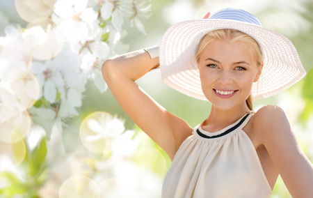 fashion, people and summer holidays concept - beautiful woman in hat and dress over green blooming garden background photo