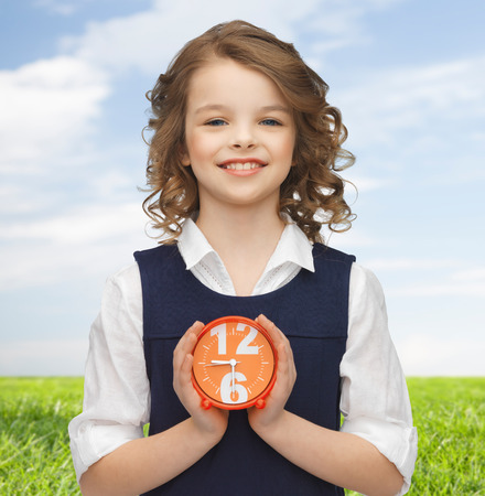 punctuality: people, childhood, time and punctuality concept - happy girl with alarm clock over blue sky and grass background