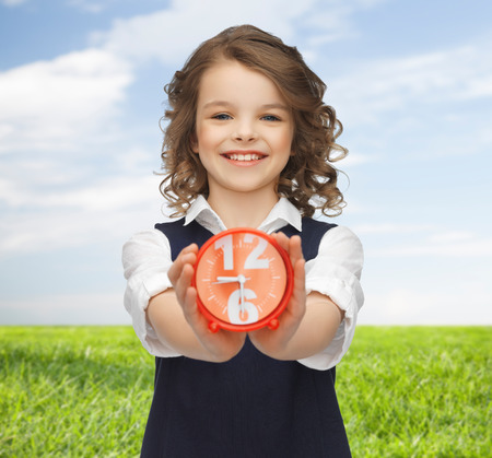 people, childhood, time and punctuality concept - happy girl with alarm clock over blue sky and grass background photo