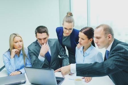 trabajo en equipo: negocios, tecnolog�a y el concepto de trabajo en equipo - equipo de negocios serio con los ordenadores port�tiles, documentos y caf� con la discusi�n en la oficina Foto de archivo