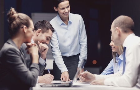 training seminar: business, technology, management and people concept - smiling female boss talking to business team in office Stock Photo