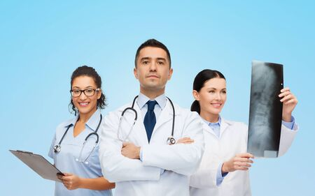 medics: surgery, profession, people and medicine concept - group of medics with x-ray over blue background