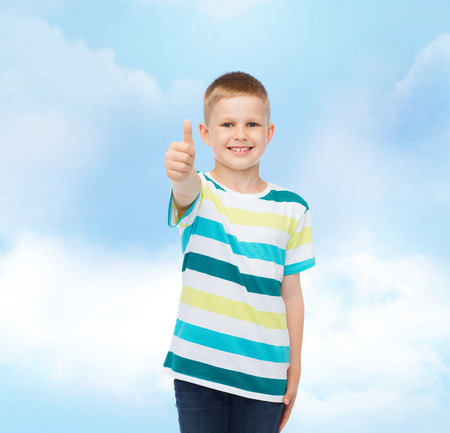 pre approval: happiness, childhood and people concept - smiling little boy in casual clothes showing thumbs up over cloudy sky background