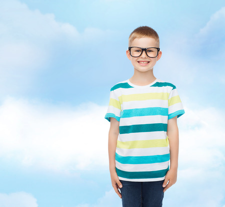 pre adolescent boy: vision, education, childhood and school concept - smiling little boy in eyeglasses over blue sky with white clouds background