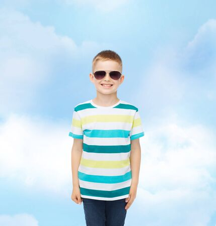 pre teen boy: happiness, summer, childhood and people concept - smiling cute little boy in sunglasses over blue cloudy sky background Stock Photo