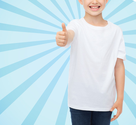 pre approval: advertising, people and childhood concept - close up of smiling little boy in white blank t-shirt showing thumbs up over blue burst rays background Stock Photo