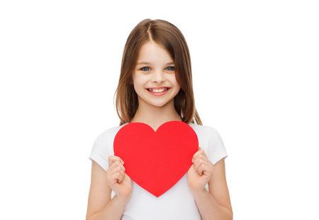 pequeño: el amor, la felicidad y el concepto de la gente - niña sonriente con el corazón rojo