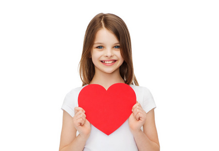 preteen: love, happiness and people concept - smiling little girl with red heart