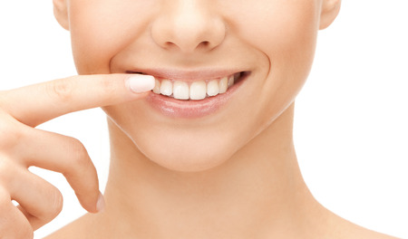 white teeth: dental health concept - beautiful woman pointing to her teeth