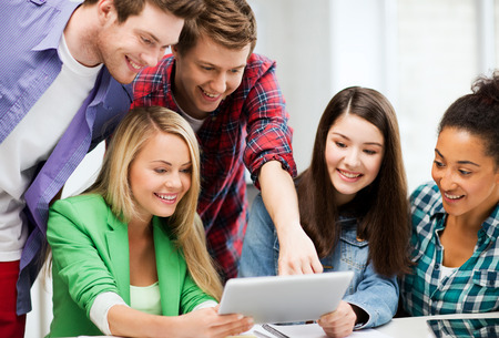 students in classroom: education and internet - smiling students looking at tablet pc in lecture at school Stock Photo