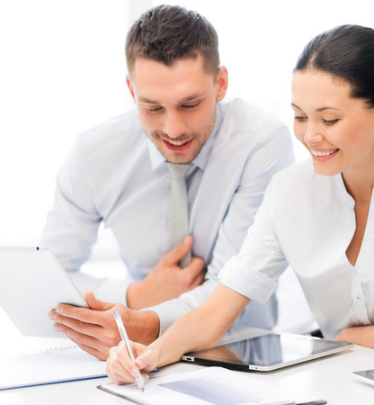 co workers: friendly business team with tablet pcs having discussion in office Stock Photo