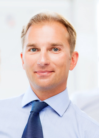 male face profile: picture of smiling handsome businessman in office