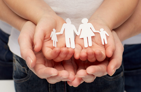 adoption: people, charity, family and care concept - close up of woman and girl hands holding paper family cutout