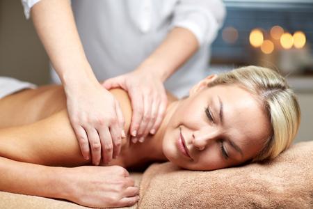 personas, belleza, spa, estilo de vida saludable y la relajación concepto - cerca de la hermosa mujer joven tendido con los ojos cerrados y con masaje de manos en el spa