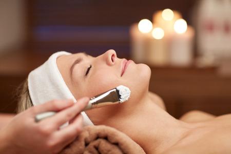 tratamientos faciales: personas, belleza, spa, cosmetolog�a y cuidado de la piel concepto - cerca de la hermosa mujer joven tendido con los ojos cerrados y cosmet�loga que aplican la m�scara facial con brocha en el spa