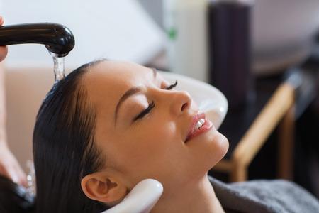 美しさと人々 のコンセプト - 美容室ヘアサロンで頭を洗うと幸せな若い女 写真素材