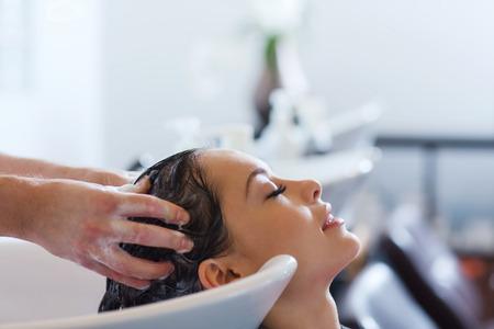 salon de belleza: la belleza y el concepto de la gente - mujer joven feliz con la cabeza de lavado peluquero en el salón de pelo