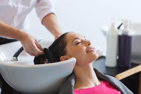 mojar: la belleza y el concepto de la gente - mujer joven feliz con la cabeza de lavado peluquero en el salón de pelo