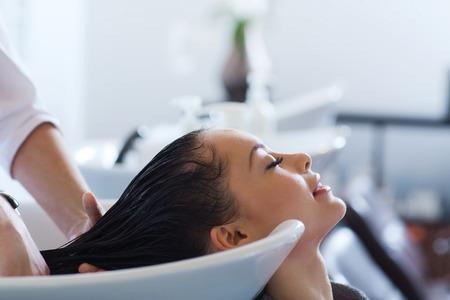 schoonheid en mensen concept - gelukkige jonge vrouw met kapper wassen hoofd bij kapsalon Stockfoto