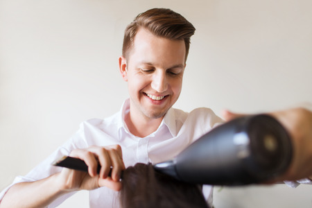 hair stylist: beauty, hairstyle and people concept - happy stylist with fan and brush making blow-dry to client at hair salon Stock Photo