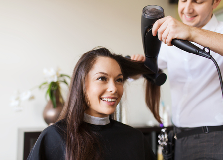 hairstyle: beauty, hairstyle and people concept - happy young woman and hairdresser with fan making hot styling at hair salon
