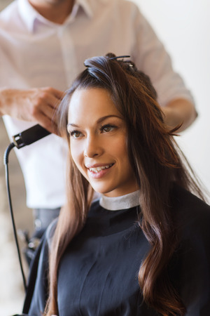 beauty, hairstyle and people concept - happy young woman with hairdresser curling hair and making hairdo at hair salon photo