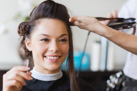 美しさ、髪型と人々 のコンセプト - 幸せな若い女性や髪鉄を作る髪型髪サロンでの美容師