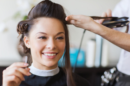 hairdressing: beauty, hairstyle and people concept - happy young woman and hairdresser with hair iron making hairdo at hair salon
