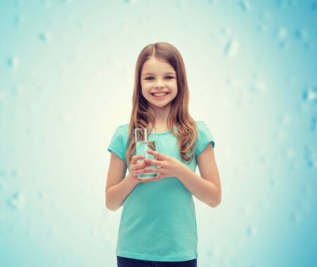 pre teen girls: health and beauty concept - smiling little girl with glass of water