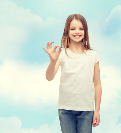 pre teen girls: happy people and gesture concept - smiling little girl in blank white t-shirt showing ok gesture