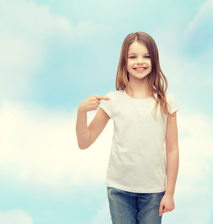 pre teens: t-shirt design concept - smiling little girl in blank white t-shirt pointing at herself