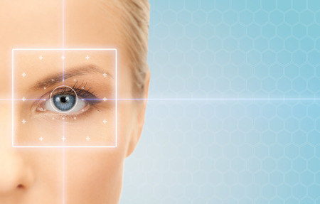 health, medicine, identity, vision and people concept - beautiful young woman with laser light lines on her eye over blue background Foto de archivo