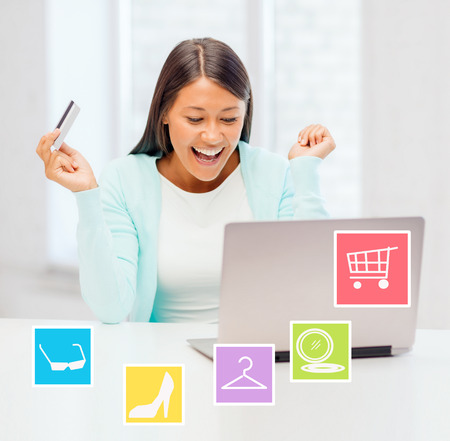 asian shopper: online shopping, sale and people concept - happy businesswoman with laptop and credit card at home