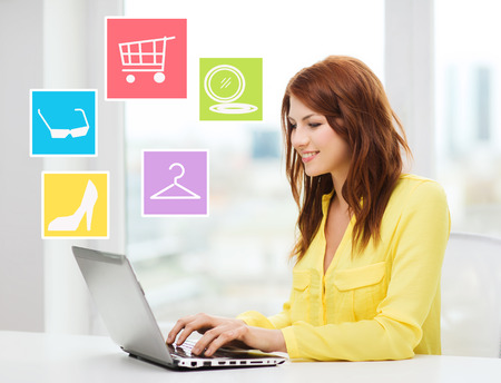 hormiga: la moda, la venta, la gente y la tecnolog�a concepto - mujer sonriente con las compras en la computadora port�til en l�nea en casa de la hormiga Foto de archivo