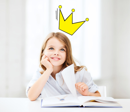 people, children, imagination and fairy tales concept - smiling girl reading book at home with castle and crown doodle over head Imagens