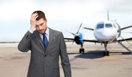 male headache: business, crisis, fail, people and travel concept - businessman having headache over airplane on runway background Stock Photo