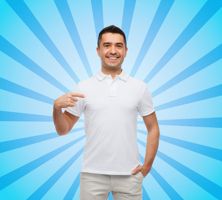 polo t shirt: happiness, advertisement, fashion, gesture and people concept - smiling man in t-shirt pointing finger on himself blue burst rays background Stock Photo