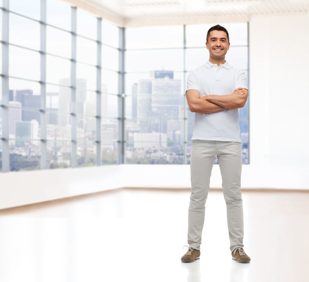 arms crossed: real estate, sale, business and people concept - smiling man with crossed arms over empty apartment or office room with big window and city view background